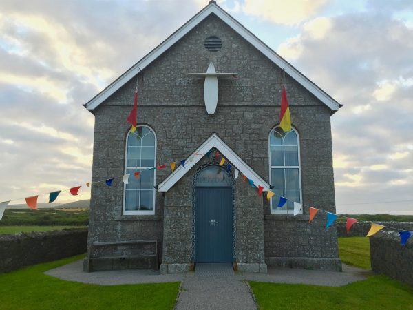 A chapel near Lands' End, Cornwall, with two surfboards for a cross. Photo by Noelle Salmi